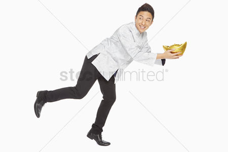 Lunar new year : Man in traditional clothing posing while holding a gold ingot