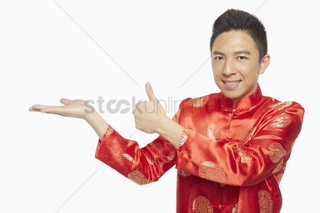 Lunar new year : Man in traditional clothing showing hand gesture