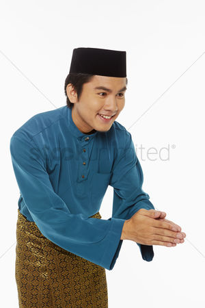 Baju melayu : Man in traditional clothing showing hand greeting gesture