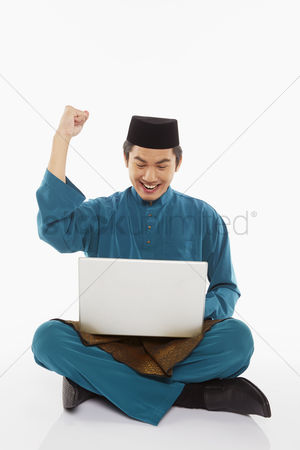Portability : Man in traditional clothing using laptop and cheering
