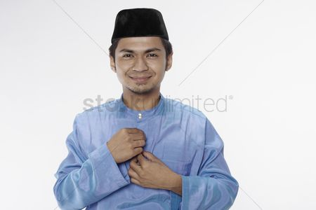 Baju melayu : Man in traditional costume buttoning his blouse