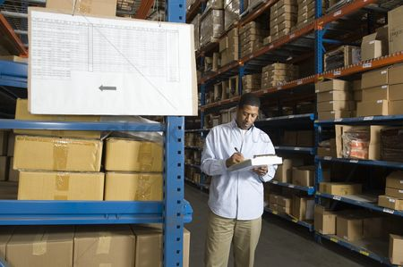 Notepad : Man inspecting boxes in distribution warehouse
