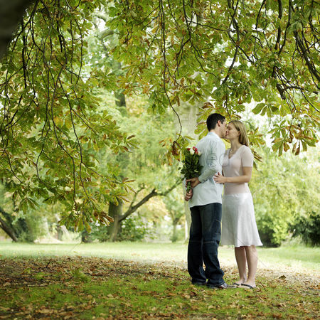Outdoor : Man kissing girlfriend while hiding a bouquet of flowers behind him