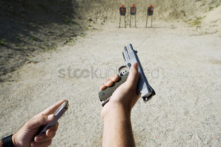 Firing : Man loading hand gun at firing range focus on hands