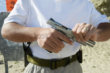 Firing : Man loading hand gun at firing range mid section