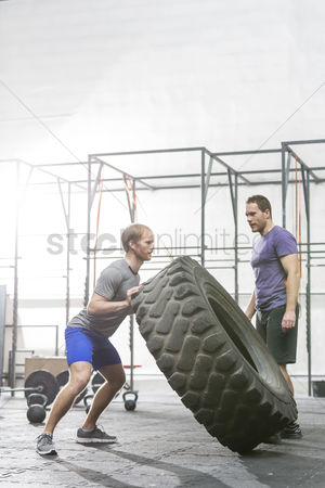 Strong : Man looking at dedicated friend flipping tire in crossfit gym