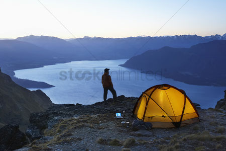 One man only : Man looking at lake next to tent at dusk