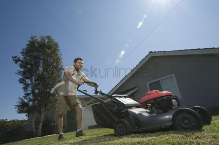 Pushing : Man moving lawn low angle