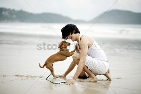 Enjoying : Man playing with his dog on the beach