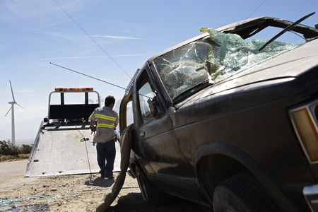 Truck : Man preparing to lift crashed car onto tow truck