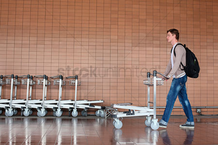 Pushing : Man pushing a cart pass a row of luggage carts in airport