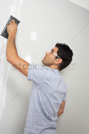 Arts : Man sanding interior wall