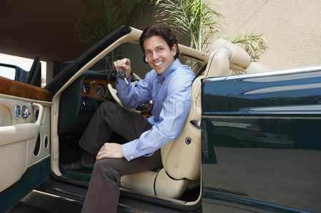 Car : Man sitting in a convertible holding car keys