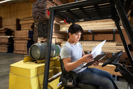 Forklift : Man sitting in forklift reading paperwork in warehouse