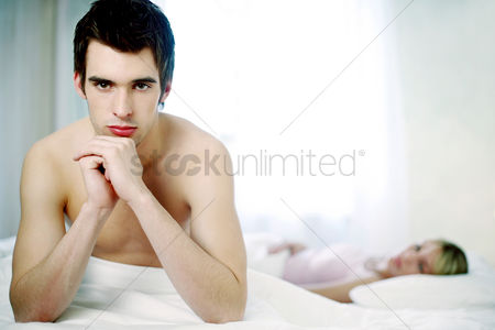 Frowning : Man sitting on the bed sulking