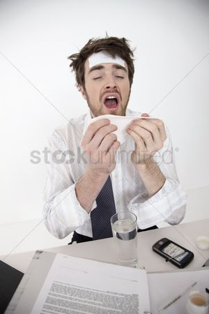 Thermometer : Man sneezing into tissue