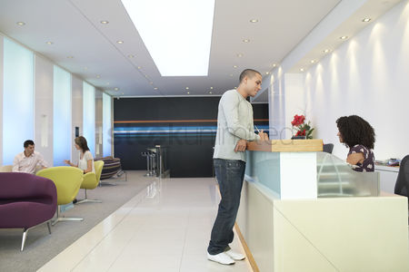 Denim : Man standing at reception desk talking to receptionist side view