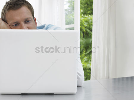 Productivity : Man staring at laptop window and garden behind