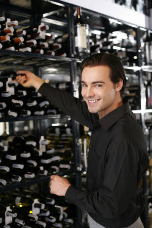 Tidy : Man taking wine bottle from the wine cellar