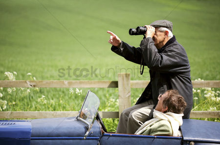 Two people : Man using binoculars while sitting in the car