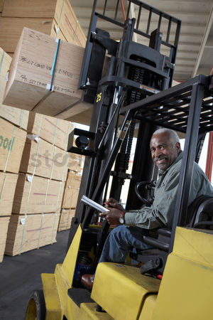 Forklift : Man using forklift to lift box in warehouse