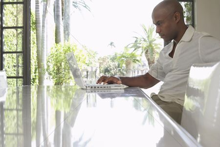 Sitting on lap : Man using laptop on dining table side view