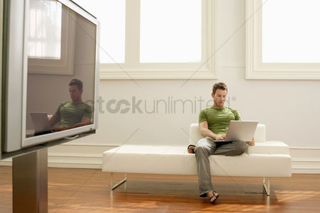 One man only : Man using laptop on modern sofa in modern apartment