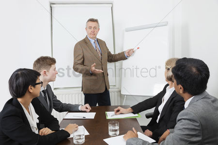 Senior women : Man using whiteboard in business meeting