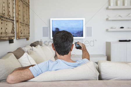 Choosing : Man watching television sitting on sofa in living room back view