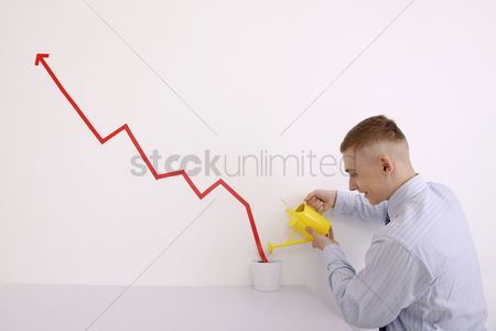 Eastern european ethnicity : Man watering pot of line graph encouraging business growth