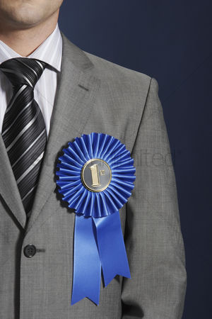 First : Man wearing blue ribbon on lapel against dark background mid section