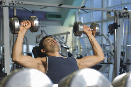 Fitness : Man weightlifting on bench with dumbbells