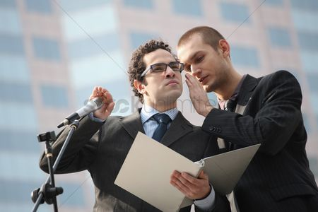 Advice : Man whispering into businessman s ear  businessman covering the microphone while listening