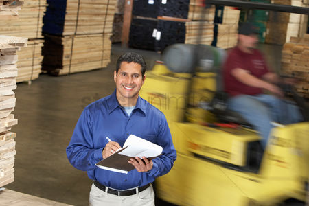 Forklift : Man with clipboard in front of forklift in warehouse