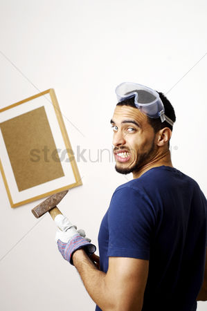 Strong : Man with goggles holding a hammer