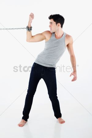 Forbidden : Man with hand tied to a chain  pulling hard