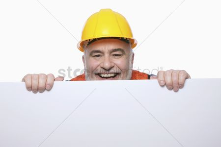 Expertise : Man with hardhat peeping from behind a placard