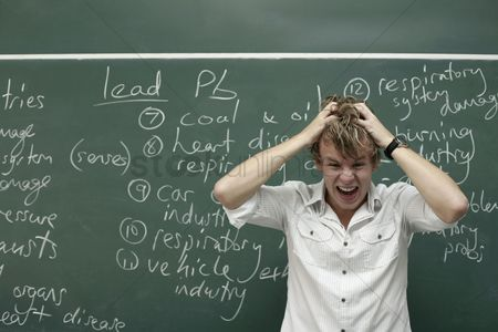 Knowledge : Man with head in hands standing in front of blackboard