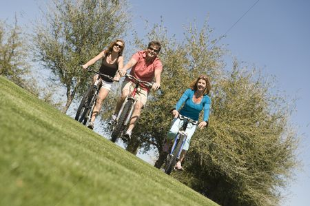 Women group outside : Man with two women cycling in park