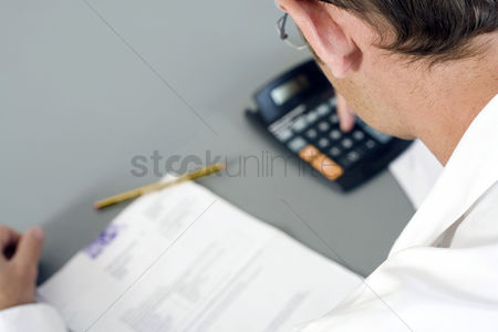 High angle view : Man working out some calculations