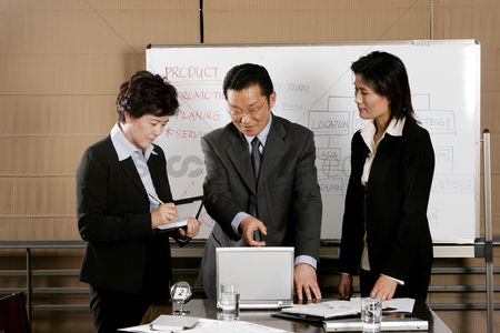 Employee : Manager showing some information on his laptop to his assistants