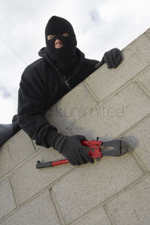 Thief : Masked thief climbing wall