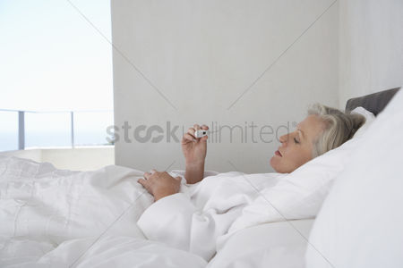 Thermometer : Mature woman lying in bed reading temperature from thermometer side view