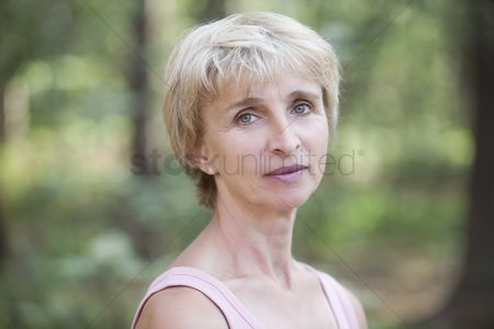 Loss : Mature woman stands in forest looking at camera