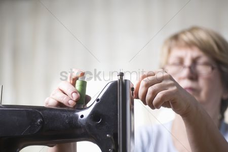 Arts : Mature woman threads sewing machine
