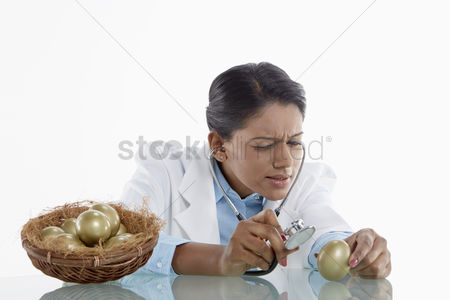 Medical personnel : Medical personnel examining a golden egg