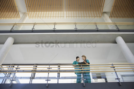 Medical : Medical workers looking at chart on balcony low angle view