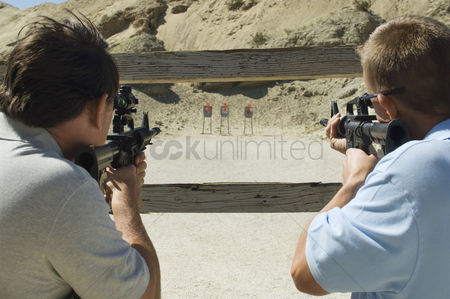 Firing : Men aiming rifles at firing range