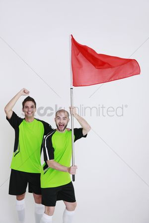 Flag : Men in football jerseys with one holding a red flag