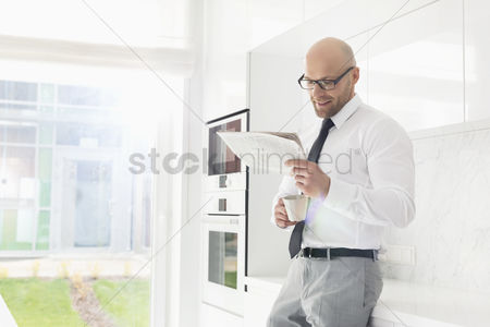 Bald : Mid adult businessman having coffee while reading newspaper at home